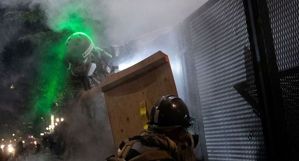 A protester standing on barriers near the fence is shot with pepper balls by federal law enforcement officers during a demonstration against police violence and racial inequality in Portland, Oregon, U.S., July 29, 2020.