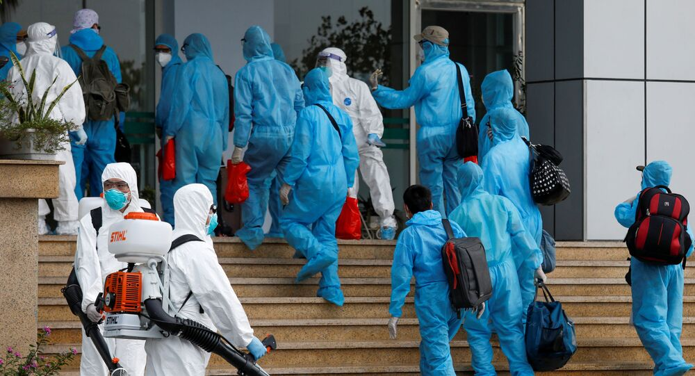 Vietnamese construction workers in blue protective suits infected with the coronavirus disease (COVID-19) arrive at the tropical diseases hospital after being repatriated from Equatorial Guinea via a specially-adapted Vietnam Airlines plane filled with medical equipment and negative pressure chambers, in Hanoi, Vietnam July 29, 2020