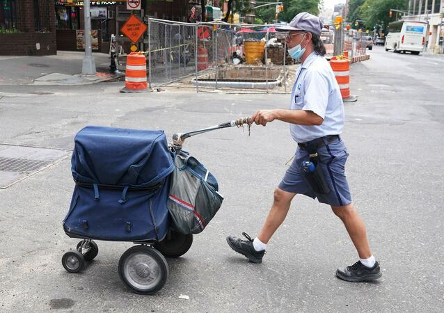 A U.S. Postal Service worker walks with his cart in the Manhattan borough of New York City, New York, U.S., July 30, 2020.