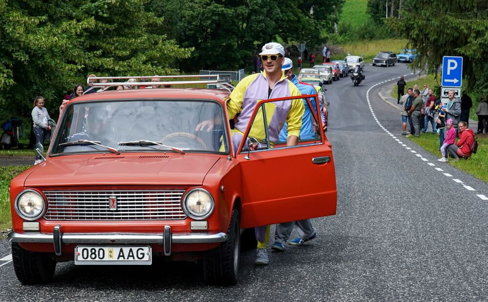 A man gets into a Lada car during a parade for the 50th anniversary of the brand in Varbuse, Estonia 25 July 2020. REUTERS/Janis Laizans