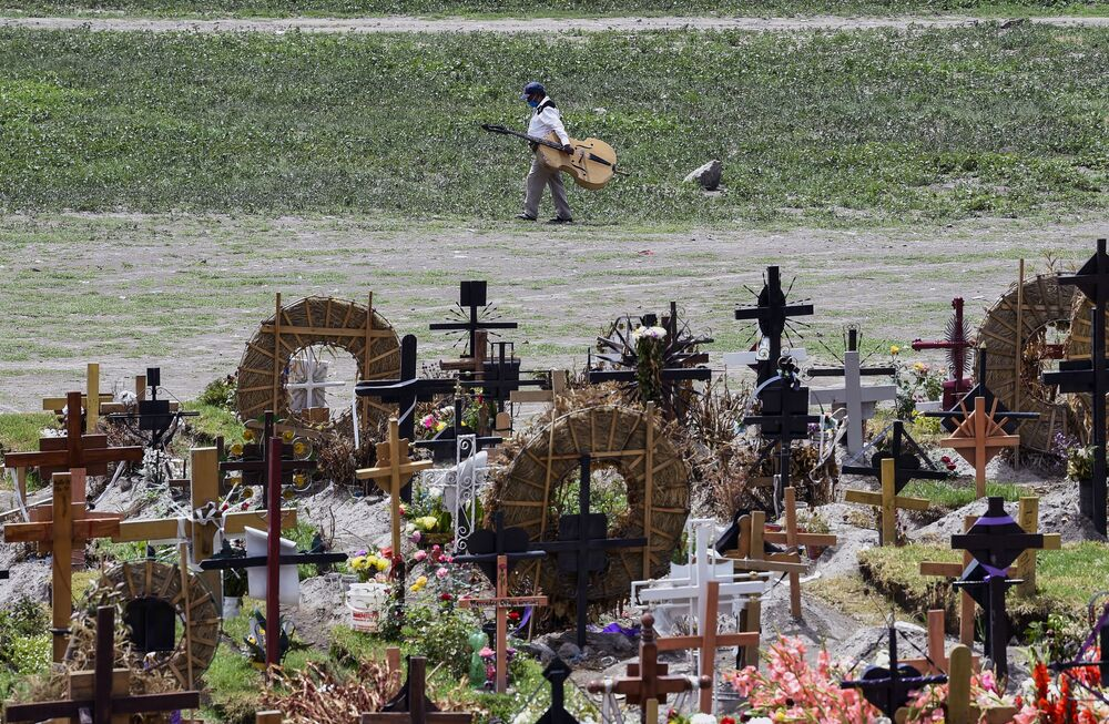 Relatives of victims killed by COVID-19 fix the graves in a special area of the Municipal Pantheon of Valle de Chalco, State of Mexico, on 28 July 2020.