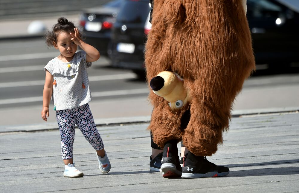 A girl looks at a street entertainer wearing a bear costume in the center of the Ukrainian capital of Kiev during a hot summer day on 24 July 2020.