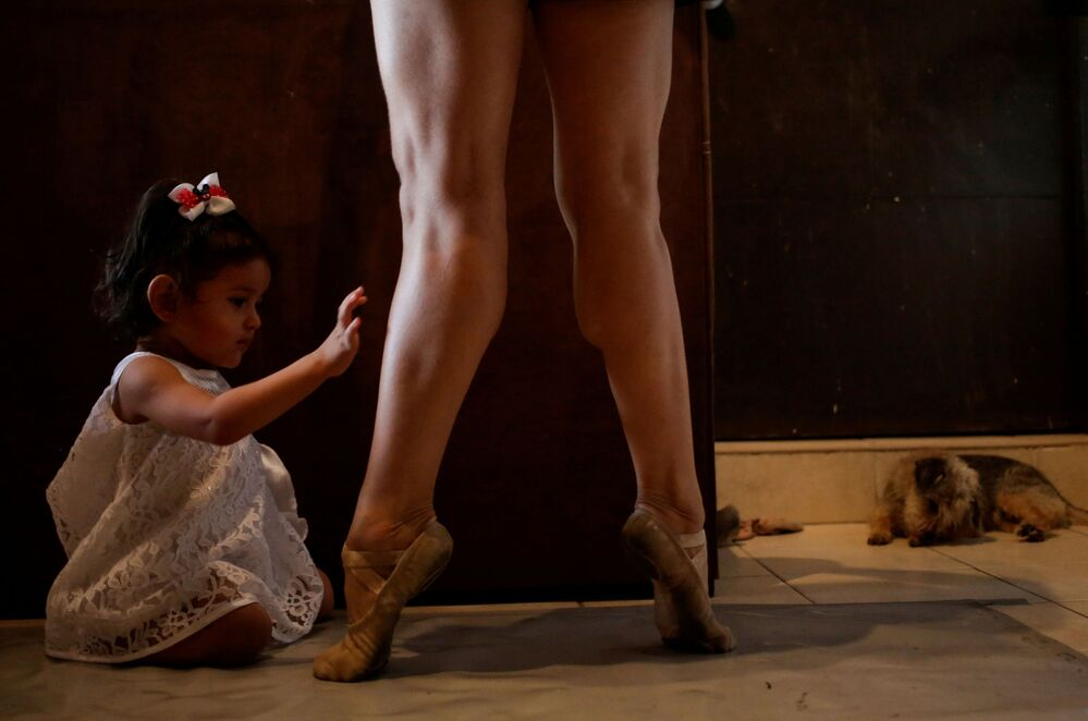 Mexican ballet dancer Abigail Miranda, member of the classic dance company Ballet de Monterrey, where some dancers were laid off due to the lack of  economic resources caused by the coronavirus disease (COVID-19) outbreak, takes part in an online training class as her daughter touches her legs at their house in Monterrey, Mexico, 11 June 2020.