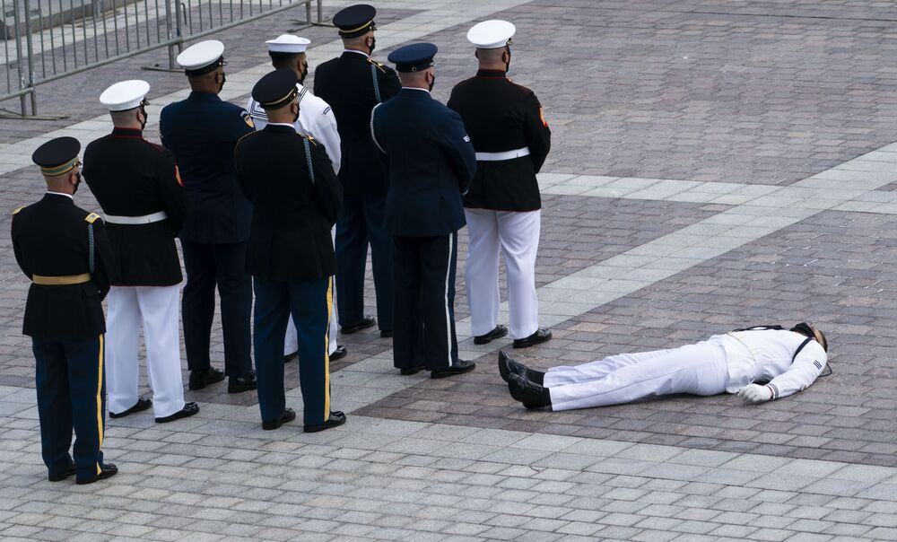 A member of the joint services military honor guard collapsed in the heat before carrying the flag-draped casket of US congressman and civil rights icon John Lewis to lie in state at the US Capitol in Washington, DC 27 July 2020.