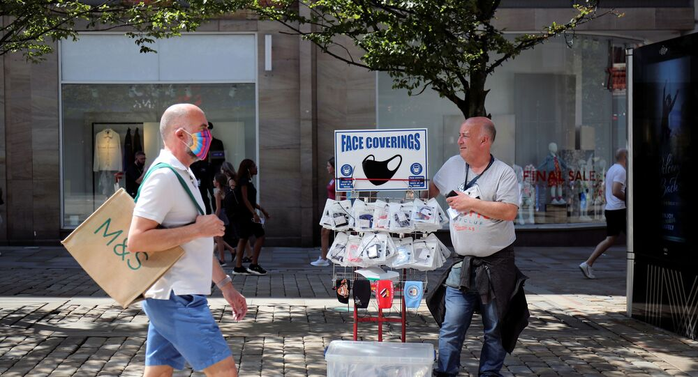 A man sells protective masks, as the city and surrounding area face local restrictions in an effort to avoid a local lockdown being forced upon the area, amid the coronavirus (COVID-19) outbreak, in Manchester