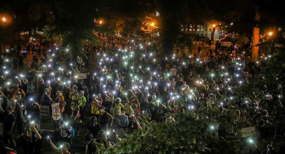People shine cellphone flashlights during a demonstration against racial inequality and police violence in Portland, Oregon, U.S., July 29, 2020.