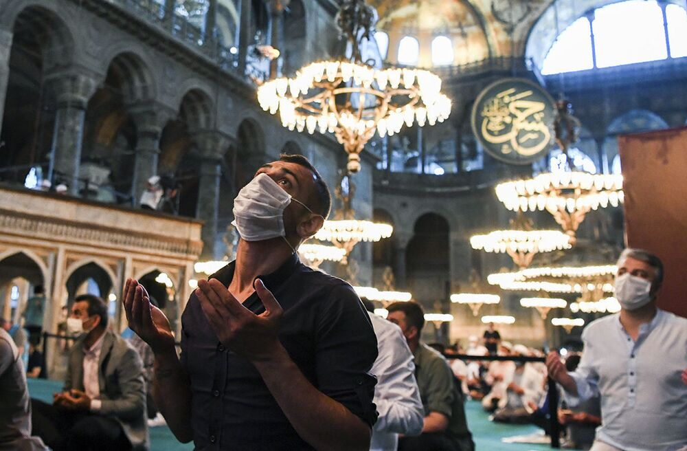 Muslims, wearing protective masks as a precaution against the coronavirus infection gather for the Eid al-Adha prayer inside the Byzantine-era Hagia Sophia, which was recently converted back to a mosque, in the historic Sultanahmet district of Istanbul, Friday, 31 July 2020.