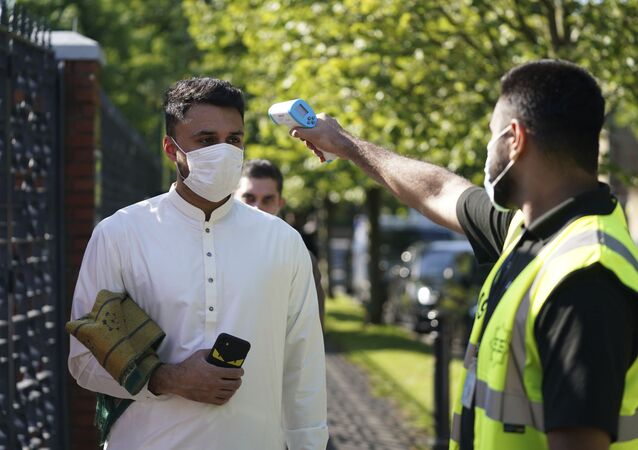 A man wearing a face mask has his temperature checked to try stop the spread of coronavirus, before being allowed to go into Manchester Central Mosque, in Manchester, northern England