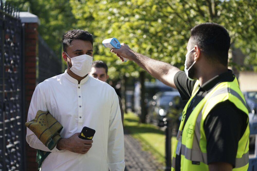 A man wearing a face mask has his temperature checked to try stop the spread of coronavirus, before being allowed to go into the Manchester Central Mosque, in Manchester, northern England, as Muslims worldwide mark the start of the Eid al-Adha holiday, Friday, 31 July 2020.