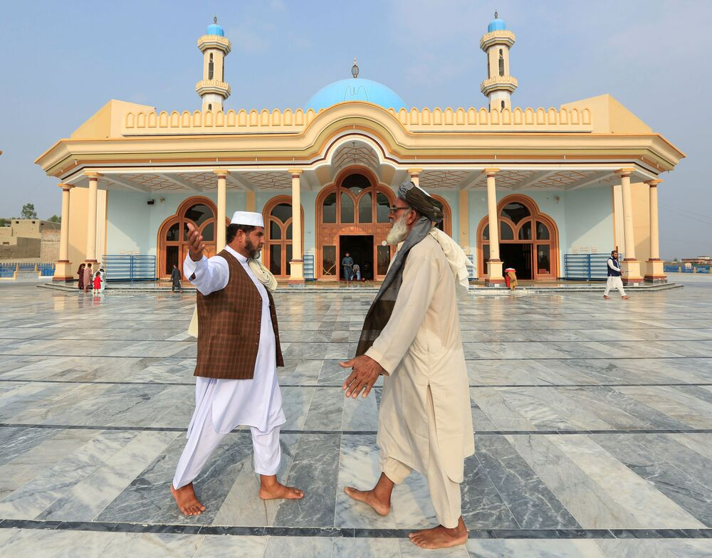 Afghan men greet each other outside a mosque after prayers during the Muslim festival of Eid al-Adha, amid the spread of the coronavirus disease (COVID-19), in Jalalabad, Afghanistan, 31 July  2020.