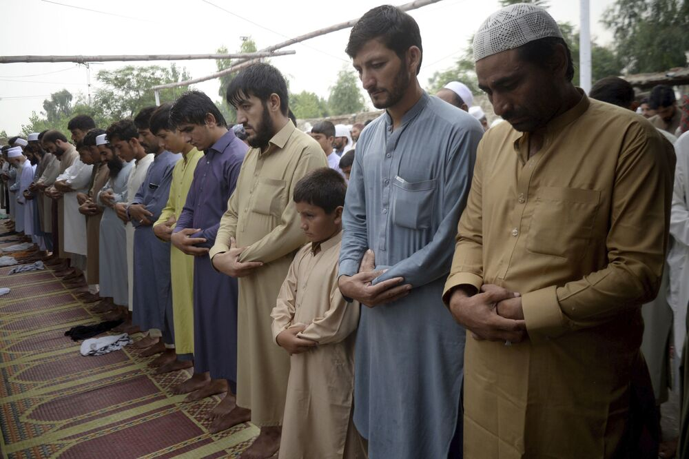 Afghan refugees offer Eid al-Adha prayers at a mosque in the Kazana refugee camp on the outskirts of Peshawar, Pakistan, Friday, 31 July 2020. During Eid al-Adha, or the Feast of Sacrifice, Muslims slaughter sheep or cattle and distribute portions of the meat to the poor.