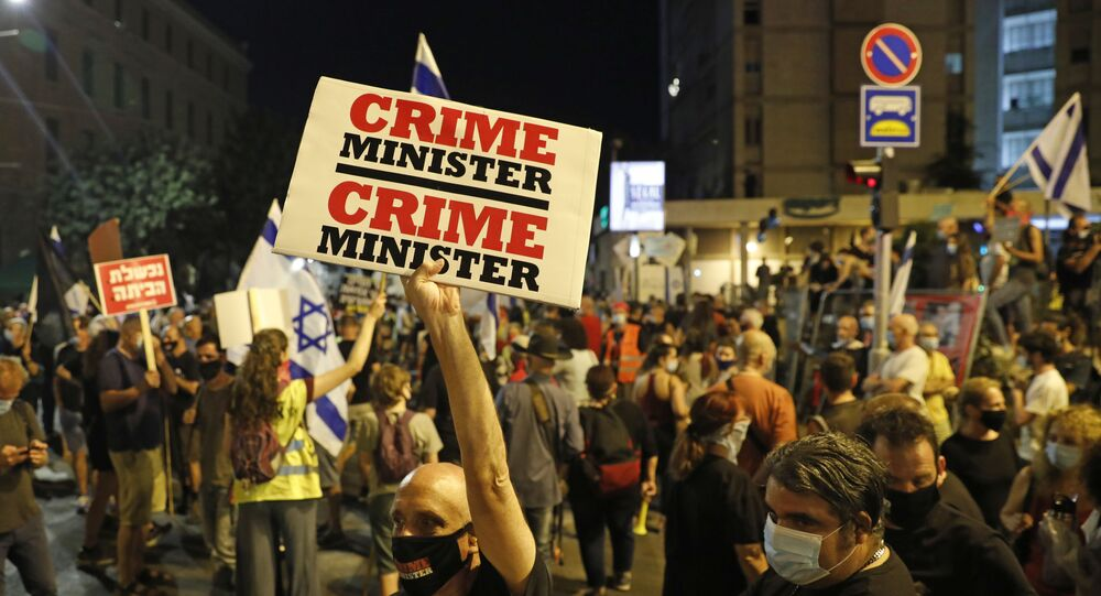 Israeli protesters hold placards as they take part in ongoing demonstrations against Prime Minister Benjamin Netanyahu in Jerusalem on July 30, 2020.