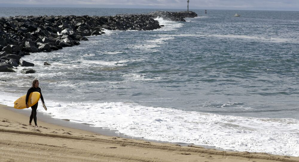 A lone surfer walks along a closed area of the beach in Newport Beach, Calif., Friday, 10 April 2020. The Wedge is closed to all surfboards and flotation devices from 10 a.m. to 5 p.m. May 1 through October 31 each year.