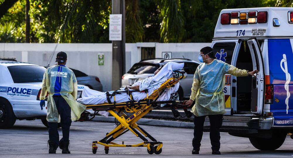 Medics transfer a patient on a stretcher from an ambulance outside of Emergency at Coral Gables Hospital where Coronavirus patients are treated in Coral Gables near Miami, on July 30, 2020.
