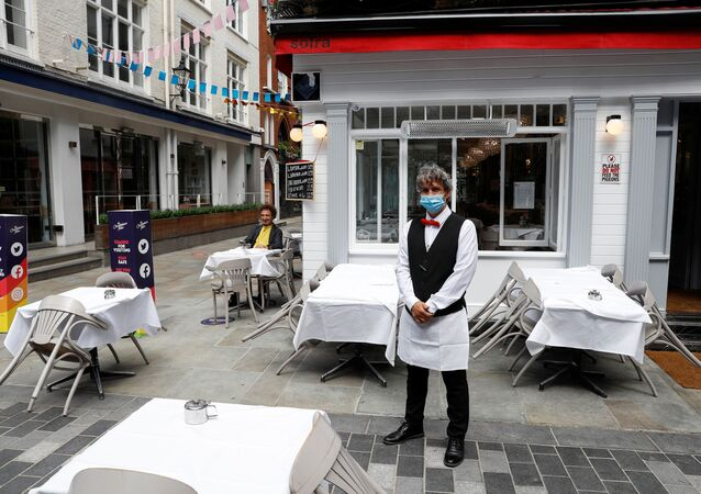 A waiter poses for photographs as he waits for customers outside a restaurant, after it reopened following the coronavirus disease (COVID-19) outbreak