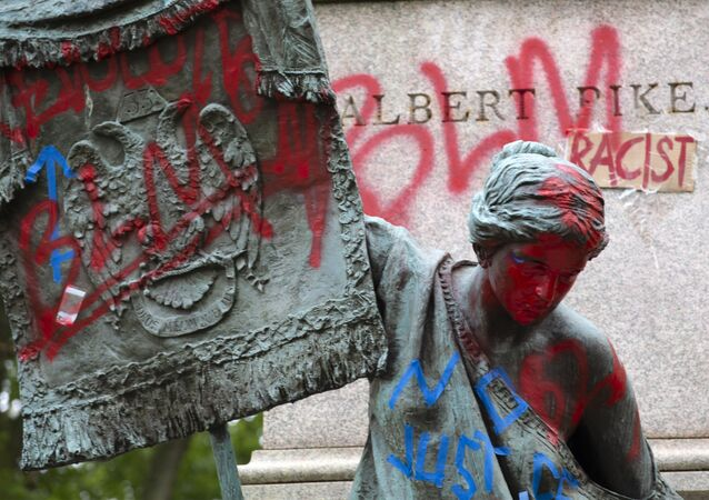 The bronze sculpture representing the Goddess of Masonry on the base of the statue of a Confederate general, Albert Pike, is seen with red paint, after protestors toppled Pike statue's and set on fire early Saturday, June 20, 2020, in Washington. It comes on Juneteenth, the day marking the end of slavery in the United States, amid continuing anti-racism demonstrations following the death of George Floyd in Minneapolis