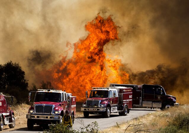 Flames flare behind fire trucks at the Apple Fire in Cherry Valley, Calif., Saturday, Aug. 1, 2020. A wildfire northwest of Palm Springs flared up Saturday afternoon, prompting authorities to issue new evacuation orders as firefighters fought the blaze in triple-degree heat