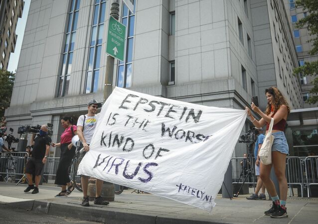 Multimedia artist Katelyn Kopenhaver, right, with help from her brother Brent Kopenhaver, unfurls a banner reading [Jefferey] Epstein is the worst kind of virus, outside federal court where a judge held a bail hearing by video for Epstein's former girlfriend Ghislaine Maxwell, Tuesday, July 14, 2020, in New York.