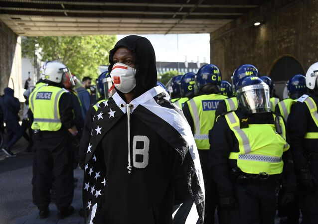 A member of Black Lives Matter movement, draped on a black and white U.S. flag, stands in front of British police officers in riot gear following a protest in central London, Saturday, June 13, 2020.