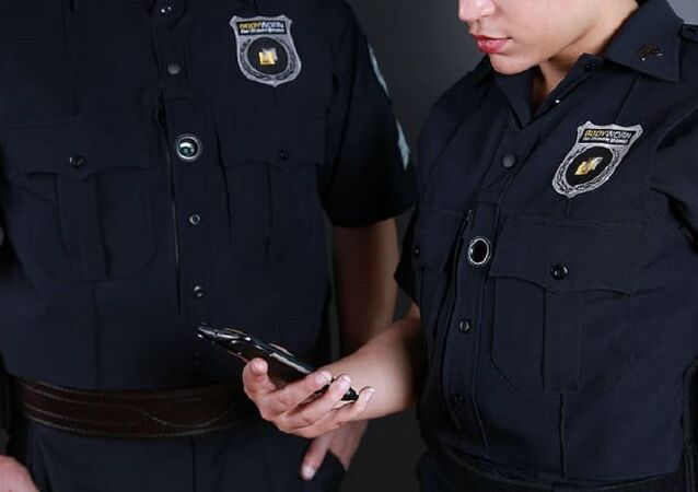 female police officer holding smartphone standing near male police officer