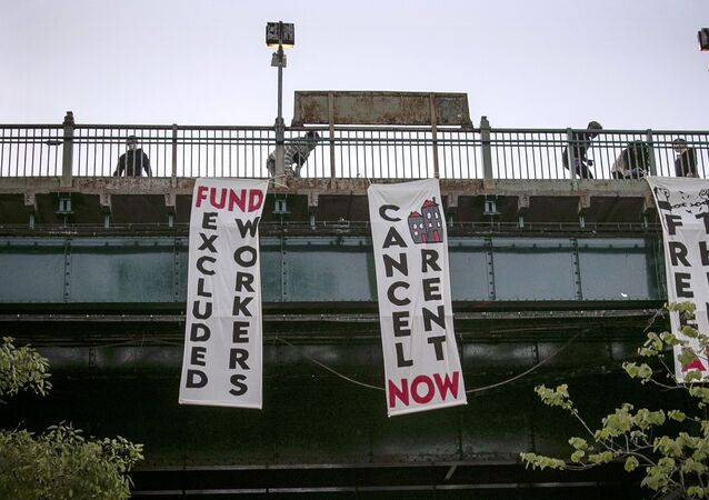 In this May 21, 2020, file photo, people from a support organization for immigrant and working class communities unfold banners, including one advocating rent cancelation, on a subway platform in the Queens borough of New York during a vigil memorializing people who died from coronavirus.