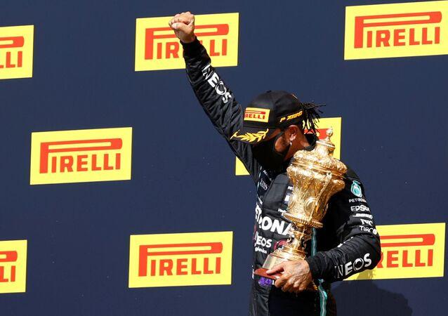 Mercedes' Lewis Hamilton celebrateswinning the race on the podium with the trophy