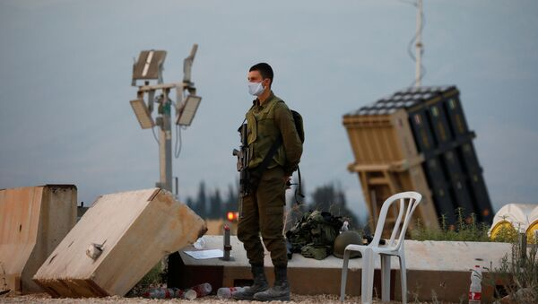 An Israeli soldier stands guard next to an Iron Dome anti-missile system near the Israel's northern border with Lebanon July 27, 2020 - Sputnik International