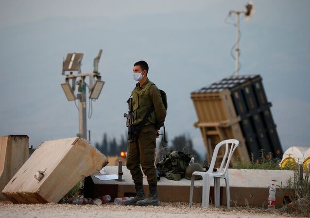 An Israeli soldier stands guard next to an Iron Dome anti-missile system near the Israel's northern border with Lebanon July 27, 2020