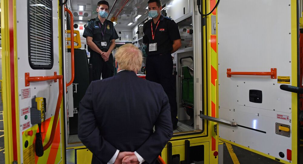 Britain's Prime Minister Boris Johnson talks with a paramedic Jack Binder and firefighter Tom Binder as he visits headquarters of the London Ambulance Service NHS Trust, amid the spread of the coronavirus disease (COVID-19), in London, Britain July 13, 2020.