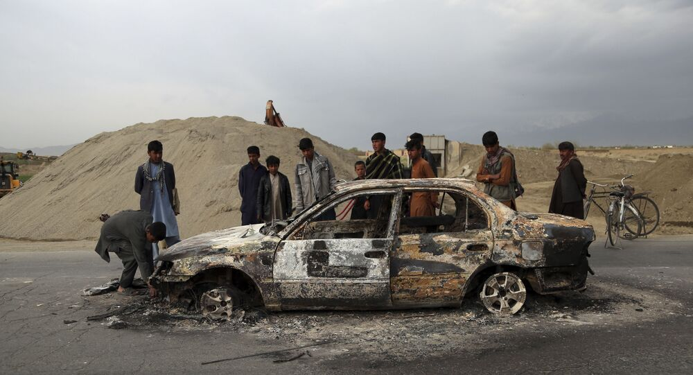 In this April 9, 2019, file photo, Afghans watch a civilian vehicle burnt after being shot by U.S. forces following an attack near the Bagram Air Base, north of Kabul, Afghanistan. Three American service members and a U.S. contractor were killed when their convoy hit a roadside bomb on Monday near the main U.S. base in Afghanistan, the U.S. forces said. The Taliban claimed responsibility for the attack. Intelligence alleging that Afghan militants might have accepted Russian bounties for killing American troops didn't scuttle the U.S.-Taliban agreement or President Donald Trump's plan to withdraw thousands more troops from the war