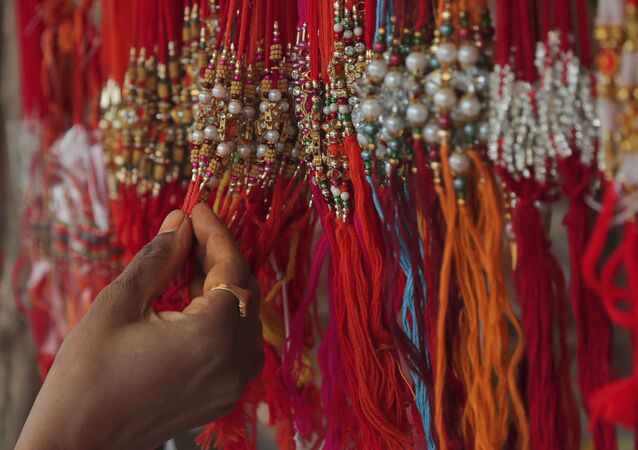 A woman shops for 'rakhi', or a sacred thread, ahead of 'Raksha Bandhan' festival in Hyderabad, India, Friday, July 31, 2020.
