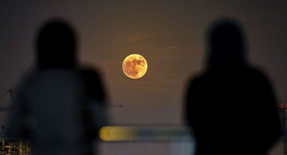 Two Iranian women watch the moon rising over Tehran in Iran (File)