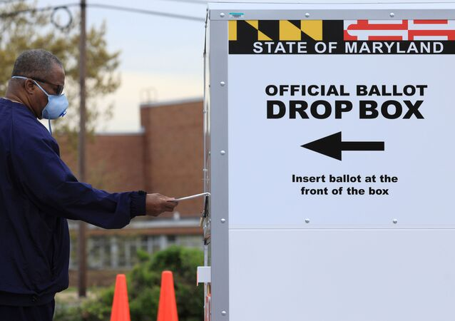 A resident drops off a mail-in ballot at the Edmondson Westside High School Polling site in Baltimore, Maryland, U.S., April 28, 2020