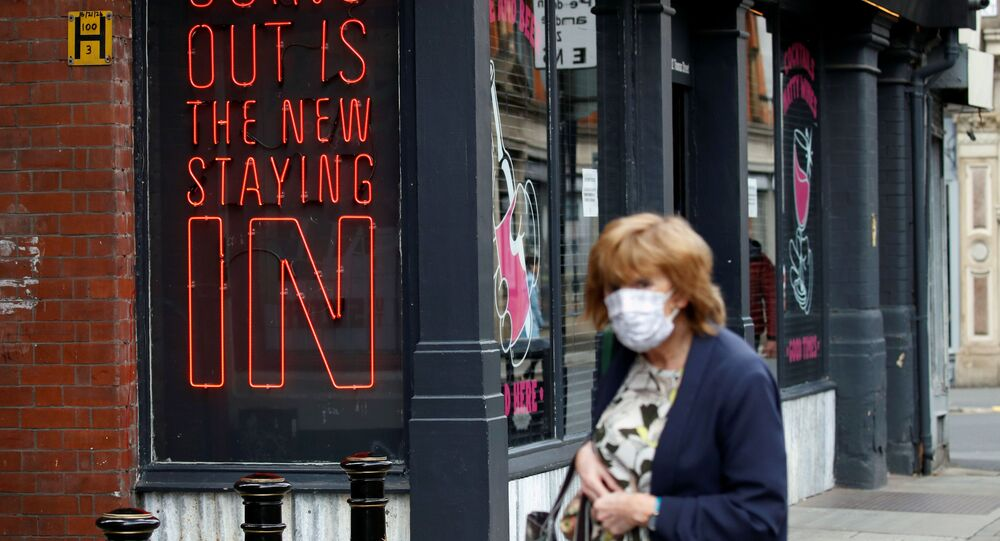 A woman wearing a protective face mask walks past a sign in Manchester