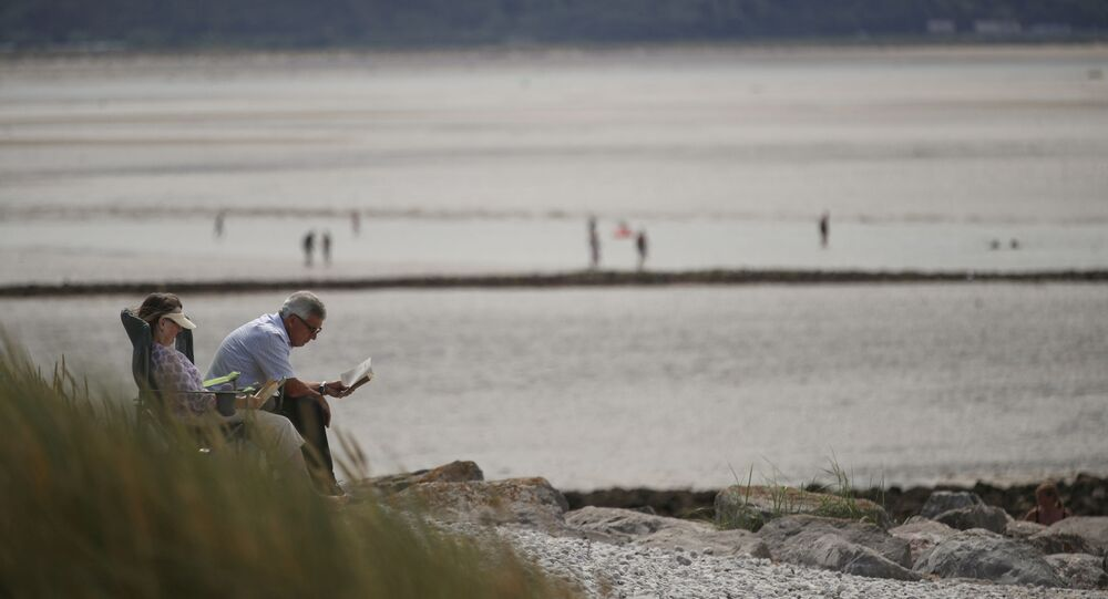 People enjoy the weather at the West Shore beach in Llandudno, Wales