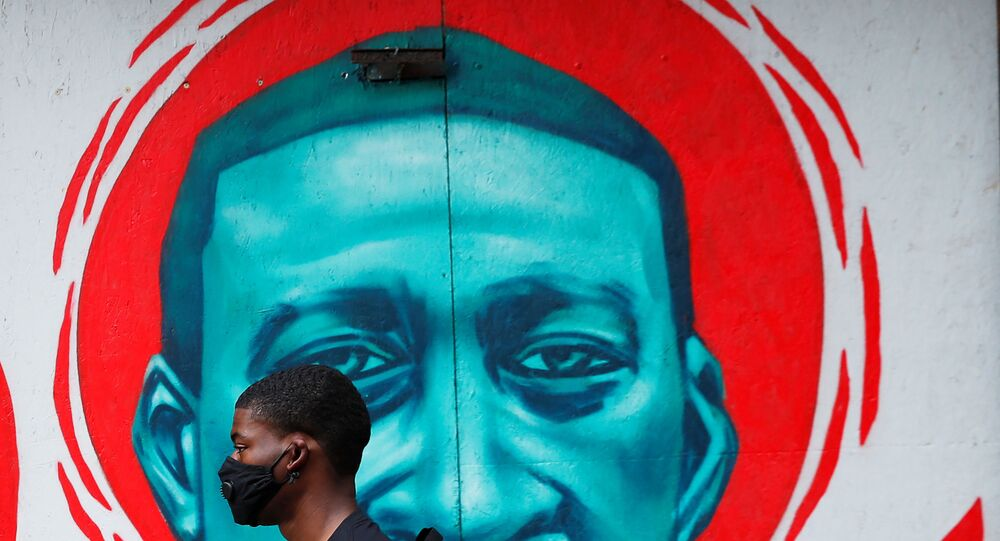 A man wearing a protective mask walks past a mural of George Floyd, in the aftermath of his death in Minneapolis police custody,  in Chicago, Illinois, U.S., July 27, 2020.