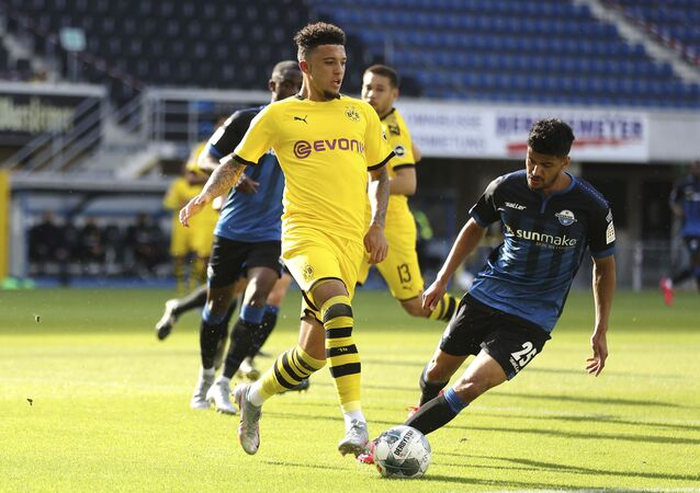 Dortmund's Jadon Sancho, left, battles for the ball with Paderborn's Mohamed Drager during a Bundesliga match in May 2020.