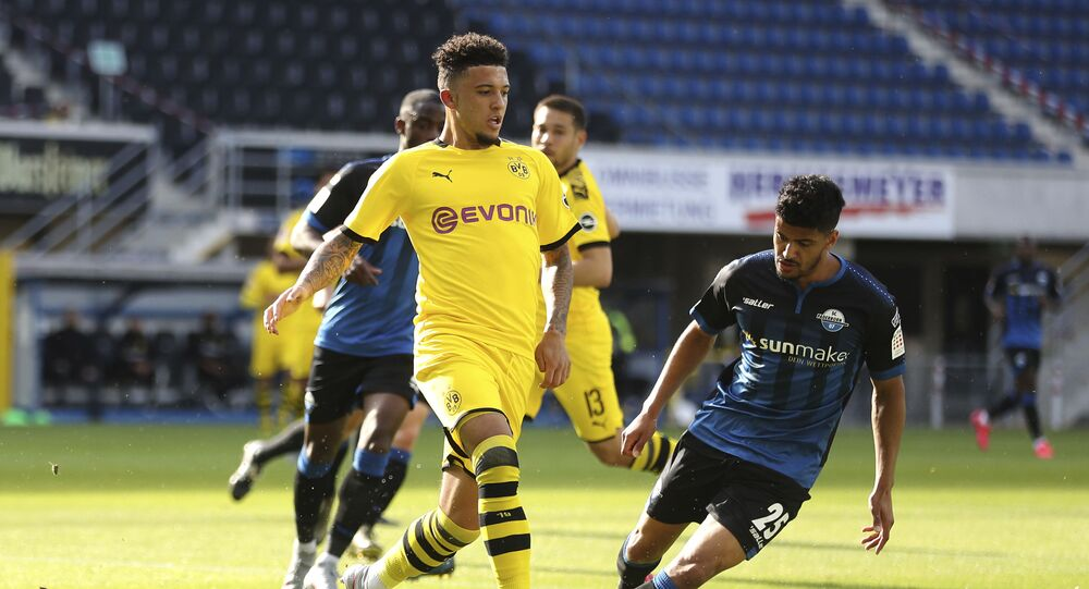 Dortmund's Jadon Sancho, left, battles for the ball with Paderborn's Mohamed Drager during a Bundesliga match in May 2020.