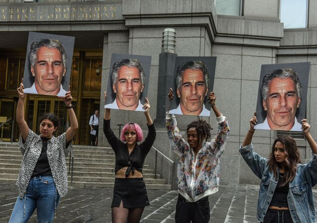A protest group called Hot Mess hold up signs of Jeffrey Epstein in front of the Federal courthouse on July 8, 2019 in New York City