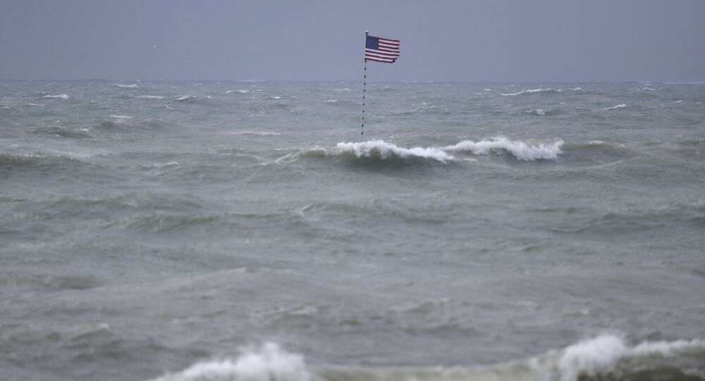An American flag flies from the shipwreck of the Breconshire, as waves churned up by Tropical Storm Isaias crash around it, Sunday, Aug. 2, 2020, in Vero Beach, Fla.