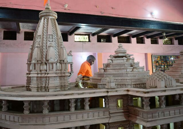 A worker walks past a model of a proposed Ram Hindu temple in Ayodhya on November 11, 2019.
