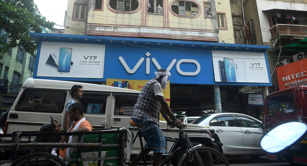 Commuters pass by an advertising board of Chinese mobile phone maker VIVO on a street in Kolkata on June 22, 2020
