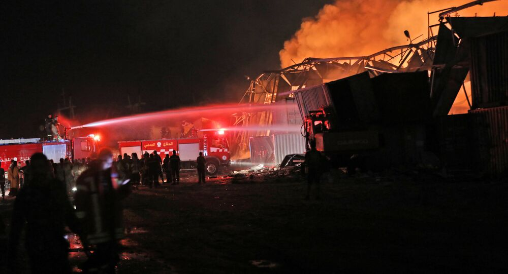Firefighters douse a blaze at the scene of an explosion at the port of Lebanon's capital Beirut on August 4, 2020