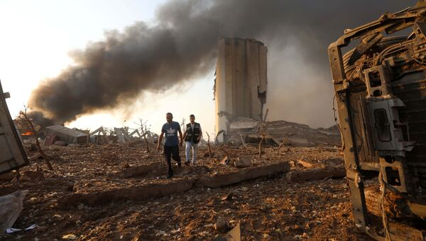 Men walk at the site of an explosion in Beirut, Lebanon August 4, 2020 - Sputnik International