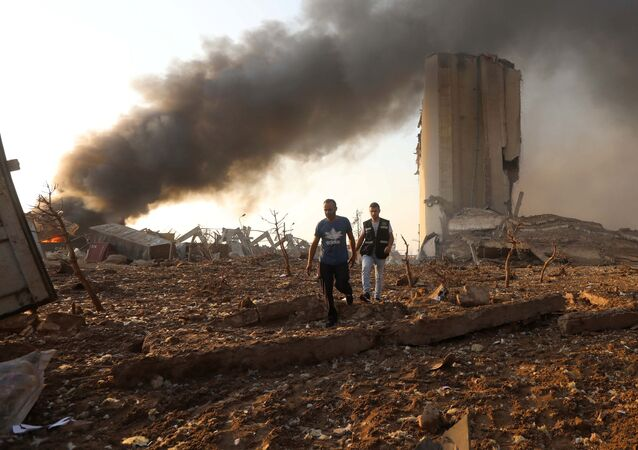 Men walk at the site of an explosion in Beirut, Lebanon August 4, 2020