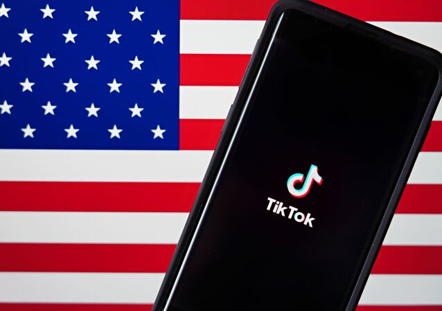 In this photo illustration, a mobile phone featuring the TikTok app is displayed next to the American flag on August 03, 2020 in New York City. Under threat of a U.S. ban on the popular social media app, it has been reported that Microsoft is considering taking over from Chinese firm ByteDance.