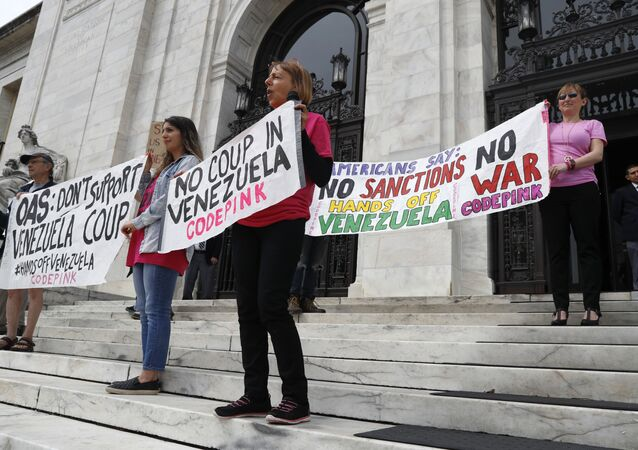 Protesters from the organization Code Pink, protest what they refer to as a coup in Venezuela, on the steps of the Organization of American States (OAS), Tuesday April 9, 2019