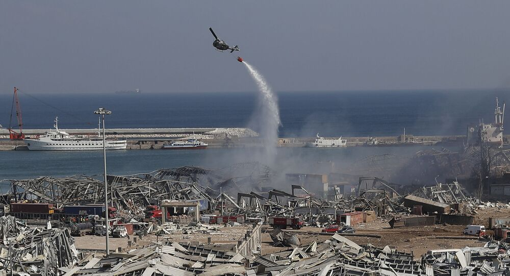 An army helicopter drops water at the scene of Tuesday's massive explosion that hit the seaport of Beirut, Lebanon, Wednesday, Aug. 5, 2020. Residents of Beirut awoke to a scene of utter devastation on Wednesday, a day after a massive explosion at the port sent shock waves across the Lebanese capital, killing dozens of people and wounding thousands.