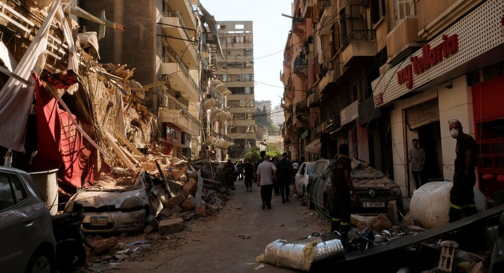 People walk past damaged buildings and vehicles following Tuesday's blast in Beirut's port area, Lebanon 5 August 2020.