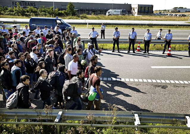 FILE - In this Sept. 9, 2015 file picture hundreds of refugees walk in Southern Jutland motorway near Padborg in Denmark